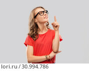 Купить «smiling student girl in glasses pointing finger up», фото № 30994786, снято 17 февраля 2019 г. (c) Syda Productions / Фотобанк Лори