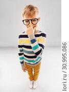 Купить «smiling boy in glasses and striped pullover», фото № 30995086, снято 9 марта 2019 г. (c) Syda Productions / Фотобанк Лори
