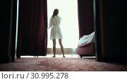 Купить «A ginger woman in bathrobe opens the curtains in hotel room», видеоролик № 30995278, снято 6 июня 2020 г. (c) Константин Шишкин / Фотобанк Лори
