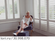 Active senior woman with hand on chin sitting on chair in a comfortable home. Стоковое фото, агентство Wavebreak Media / Фотобанк Лори