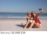 Купить «Female friends taking selfie with mobile phone on the beach», фото № 30998534, снято 15 марта 2019 г. (c) Wavebreak Media / Фотобанк Лори