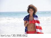 Купить «Woman wrapped in american flag looking at camera on the beach», фото № 30998662, снято 15 марта 2019 г. (c) Wavebreak Media / Фотобанк Лори