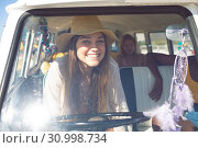 Купить «Woman looking at camera while sitting front seat of camper van at beach», фото № 30998734, снято 15 марта 2019 г. (c) Wavebreak Media / Фотобанк Лори