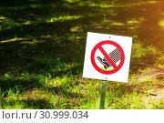 Купить «The prohibitive sign on the label Do not walk the lawn - closeup against tha lawn in sunlight», фото № 30999034, снято 6 июня 2019 г. (c) Зезелина Марина / Фотобанк Лори