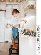 Купить «Litte boy cooking melt chocolate on the kitchen», фото № 30999054, снято 6 марта 2019 г. (c) Tryapitsyn Sergiy / Фотобанк Лори