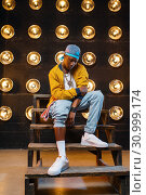 Купить «Black rapper in cap sitting on the steps», фото № 30999174, снято 5 апреля 2019 г. (c) Tryapitsyn Sergiy / Фотобанк Лори