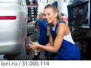 Купить «female mechanic working on car tyre service», фото № 31000114, снято 19 сентября 2019 г. (c) Яков Филимонов / Фотобанк Лори