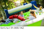 Купить «Team of friends playing with inflatable sticks on the trampoline», фото № 31000142, снято 20 июля 2019 г. (c) Яков Филимонов / Фотобанк Лори