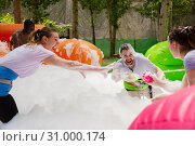 Купить «Happy friends are playing a game - who will find balls in soap suds faster», фото № 31000174, снято 22 июля 2019 г. (c) Яков Филимонов / Фотобанк Лори