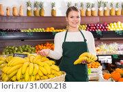 Купить «Young female in apron selling fresh bananas on the market», фото № 31000218, снято 31 января 2019 г. (c) Яков Филимонов / Фотобанк Лори