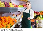Купить «Pretty female in apron selling fresh oranges», фото № 31000222, снято 29 мая 2020 г. (c) Яков Филимонов / Фотобанк Лори