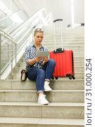 Купить «Worried girl sitting on stairs with booklet», фото № 31000254, снято 27 апреля 2018 г. (c) Яков Филимонов / Фотобанк Лори