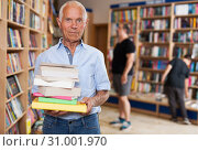 Купить «Elderly male buyer with pile of books in bookshop interior», фото № 31001970, снято 11 июня 2018 г. (c) Яков Филимонов / Фотобанк Лори
