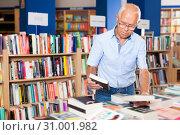 Купить «Portrait of intelligent older man choosing necessary books on shelves in library», фото № 31001982, снято 11 июня 2018 г. (c) Яков Филимонов / Фотобанк Лори
