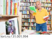Купить «Older man choosing books in bookstore», фото № 31001994, снято 11 июня 2018 г. (c) Яков Филимонов / Фотобанк Лори