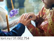 Купить «Groom and bride on the wedding engagement ceremony in orthodox church», фото № 31002754, снято 24 мая 2019 г. (c) Дмитрий Калиновский / Фотобанк Лори