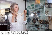 Купить «Woman trying on a gemstone necklace and earrings at a jewelry store», фото № 31003962, снято 2 мая 2019 г. (c) Яков Филимонов / Фотобанк Лори