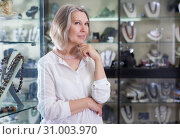 Купить «Adult woman trying on a rose quartz necklace and earrings at a jewelry store», фото № 31003970, снято 2 мая 2019 г. (c) Яков Филимонов / Фотобанк Лори