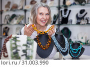 Adult woman chooses jewelry from turquoise and amber jewelery in the store. Стоковое фото, фотограф Яков Филимонов / Фотобанк Лори