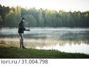 Купить «fishing. fisher with spinning rod early morning», фото № 31004798, снято 8 мая 2019 г. (c) Дмитрий Калиновский / Фотобанк Лори
