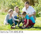 Young family with two kids placing a new tree. Стоковое фото, фотограф Яков Филимонов / Фотобанк Лори