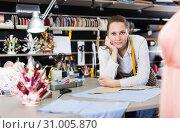 Купить «Portrait of woman designer who is standing on her workplace in time designing new collection», фото № 31005870, снято 5 мая 2018 г. (c) Яков Филимонов / Фотобанк Лори