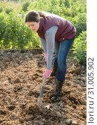 Купить «Female holding shovel at organic plantation», фото № 31005902, снято 21 февраля 2019 г. (c) Яков Филимонов / Фотобанк Лори