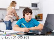 Boy doing homework, mother cooking. Стоковое фото, фотограф Яков Филимонов / Фотобанк Лори