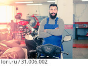 Купить «Positive male worker showing motorbikes in workplace», фото № 31006002, снято 20 июля 2019 г. (c) Яков Филимонов / Фотобанк Лори