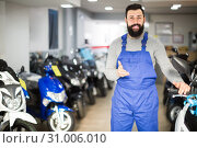 Купить «vigorous man worker displaying various motorcycles in workshop», фото № 31006010, снято 20 июля 2019 г. (c) Яков Филимонов / Фотобанк Лори