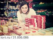 Купить «Female shopper searching for sweets», фото № 31006086, снято 23 ноября 2016 г. (c) Яков Филимонов / Фотобанк Лори
