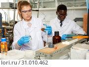 Купить «Young woman scientist working in research laboratory performing experiments», фото № 31010462, снято 21 марта 2019 г. (c) Яков Филимонов / Фотобанк Лори