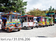 GUATAPE, ANTIOQUIA - COLOMBIA, NOVEMBER 2017. Motor-tricycles decorated as traditional Colombian chivas at the colorful Guatape city. Стоковое фото, фотограф YAY Micro / easy Fotostock / Фотобанк Лори