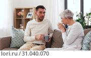 Купить «adult son and senior mother drink coffee at home», видеоролик № 31040070, снято 25 июня 2019 г. (c) Syda Productions / Фотобанк Лори