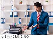 Купить «Young employee making copies at copying machine», фото № 31043990, снято 14 декабря 2018 г. (c) Elnur / Фотобанк Лори