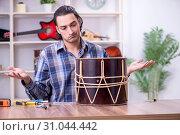 Купить «Young handsome repairman repairing drum», фото № 31044442, снято 4 апреля 2019 г. (c) Elnur / Фотобанк Лори