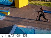 Купить «Мальчик катается самокате на площадке скейтпарка в Парке технических видов спорта в районе Печатники города Москвы, Россия», фото № 31084838, снято 18 июня 2019 г. (c) Николай Винокуров / Фотобанк Лори