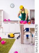Купить «Young male contractor doing housework after party», фото № 31094878, снято 14 марта 2019 г. (c) Elnur / Фотобанк Лори