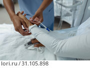 Female doctor attaching iv drip on female patient hand. Стоковое фото, агентство Wavebreak Media / Фотобанк Лори