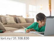 Купить «Boy using laptop while drawing a sketch on book at home», фото № 31108830, снято 19 марта 2019 г. (c) Wavebreak Media / Фотобанк Лори