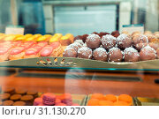 Купить «Many chocolate cakes and eclairs on showcase in cafe. Chocolate balls and eclairs with red and yellow glaze. Shallow depth of field. Toned.», фото № 31130270, снято 5 апреля 2020 г. (c) easy Fotostock / Фотобанк Лори