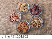 Купить «Peanuts, almonds, dates and pistachio in glass bowls on canvas», фото № 31204802, снято 5 февраля 2017 г. (c) easy Fotostock / Фотобанк Лори