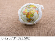 Купить «Globe wrapped with paper placed on canvas background», фото № 31323502, снято 29 октября 2017 г. (c) easy Fotostock / Фотобанк Лори