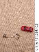 Купить «Key and a red toy car on a linen canvas», фото № 31324402, снято 7 апреля 2017 г. (c) easy Fotostock / Фотобанк Лори