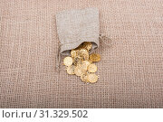 Купить «Fake gold coins out of a little sack on canvas», фото № 31329502, снято 26 ноября 2017 г. (c) easy Fotostock / Фотобанк Лори