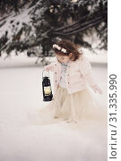 Купить «Little girl wearing a beige coat and long dress, looking at lamp with candle standing among the branches, covered with snow in the park in winter time. Little girl with lightning in frozen forest», фото № 31335990, снято 28 февраля 2018 г. (c) easy Fotostock / Фотобанк Лори