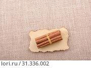 Купить «Bundle of cinnamon sticks on a linen canvas background», фото № 31336002, снято 4 мая 2017 г. (c) easy Fotostock / Фотобанк Лори