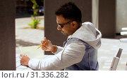 Купить «man with notebook and coffee at street cafe», видеоролик № 31336282, снято 30 июня 2019 г. (c) Syda Productions / Фотобанк Лори
