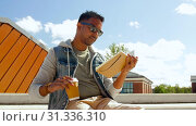 Купить «indian man with notebook or sketchbook on roof top», видеоролик № 31336310, снято 30 июня 2019 г. (c) Syda Productions / Фотобанк Лори