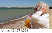 Купить «senior woman drinking shake on summer beach», видеоролик № 31379358, снято 1 июля 2019 г. (c) Syda Productions / Фотобанк Лори